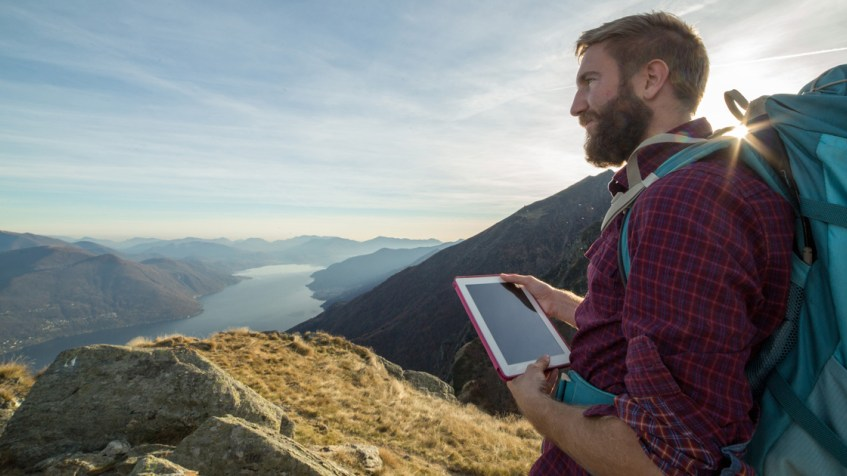 Man using tablet on mountain